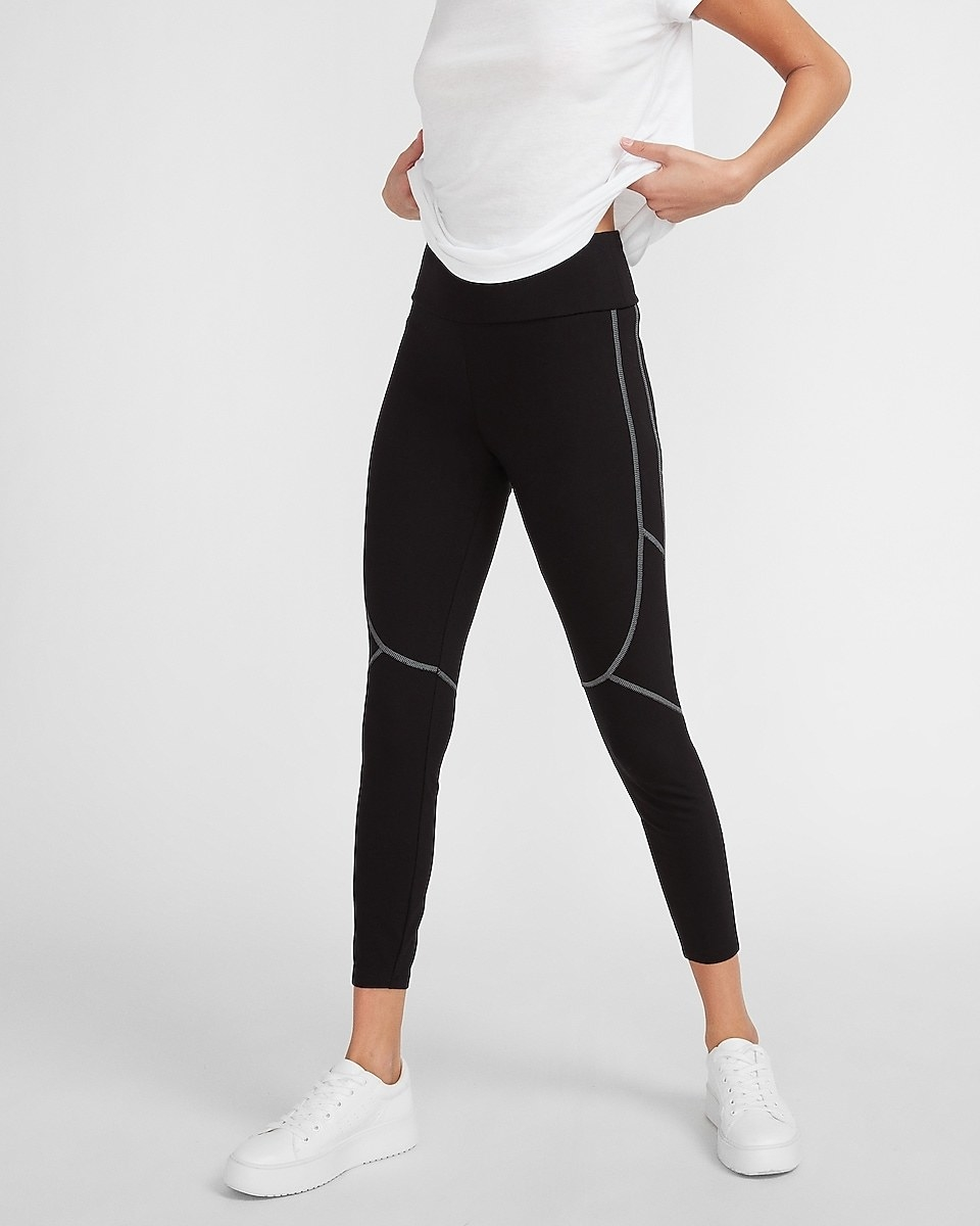 model wearing the high-waisted ankle-length leggings in black with white stitching along the outer thigh and leg