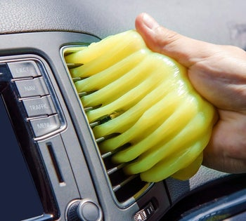 a person using the cleaning gel to clean their car vent