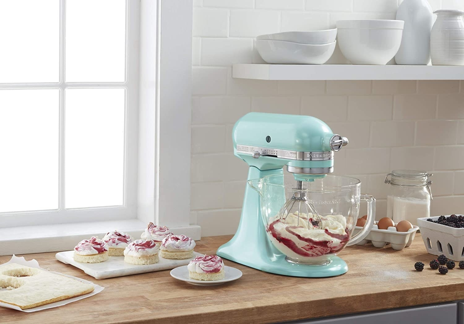 A stand mixer with icing in the bowl and other little biscuits with icing on top next to it