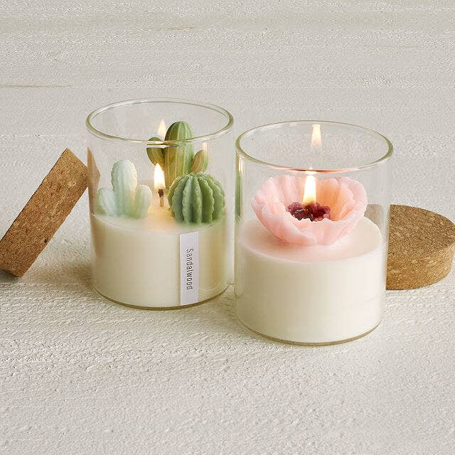 glass candle holder with a cork top and white wax, and either three wax cacti or a wax flower on top