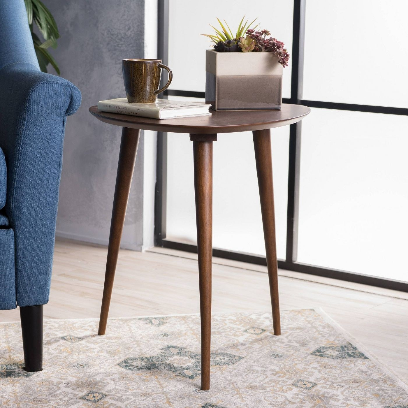 The table in the walnut finish next to a blue chair