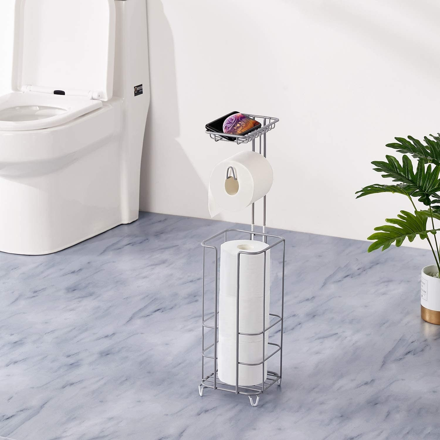 The toilet paper stand between a toilet and a plant