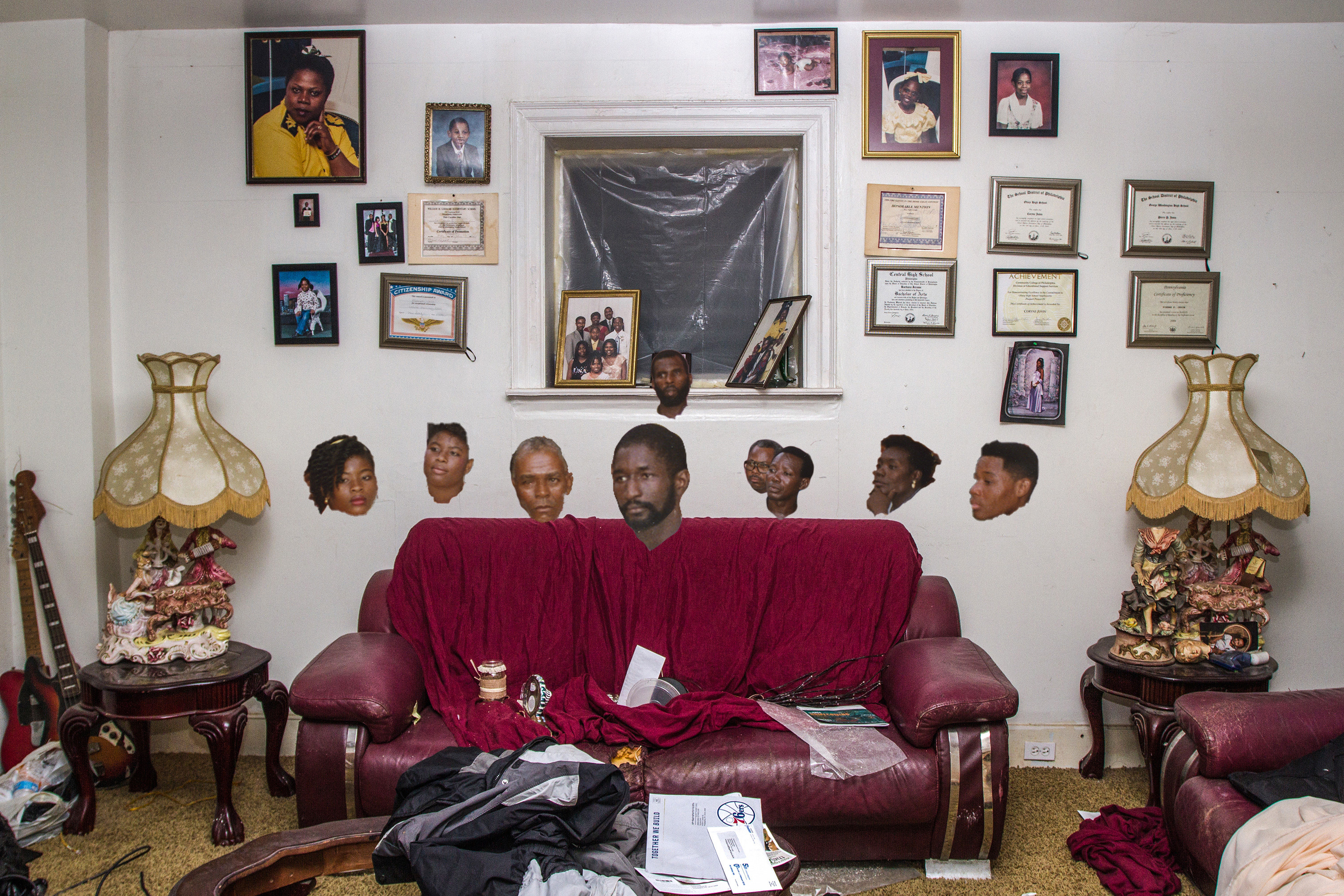 A collage of heads with no bodies hovering over a couch in a living room with pictures on the walls