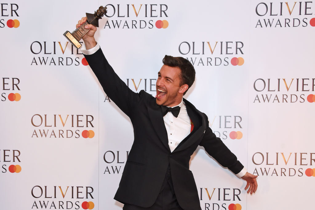 Jonathan Bailey holding his Olivier Award and smiling