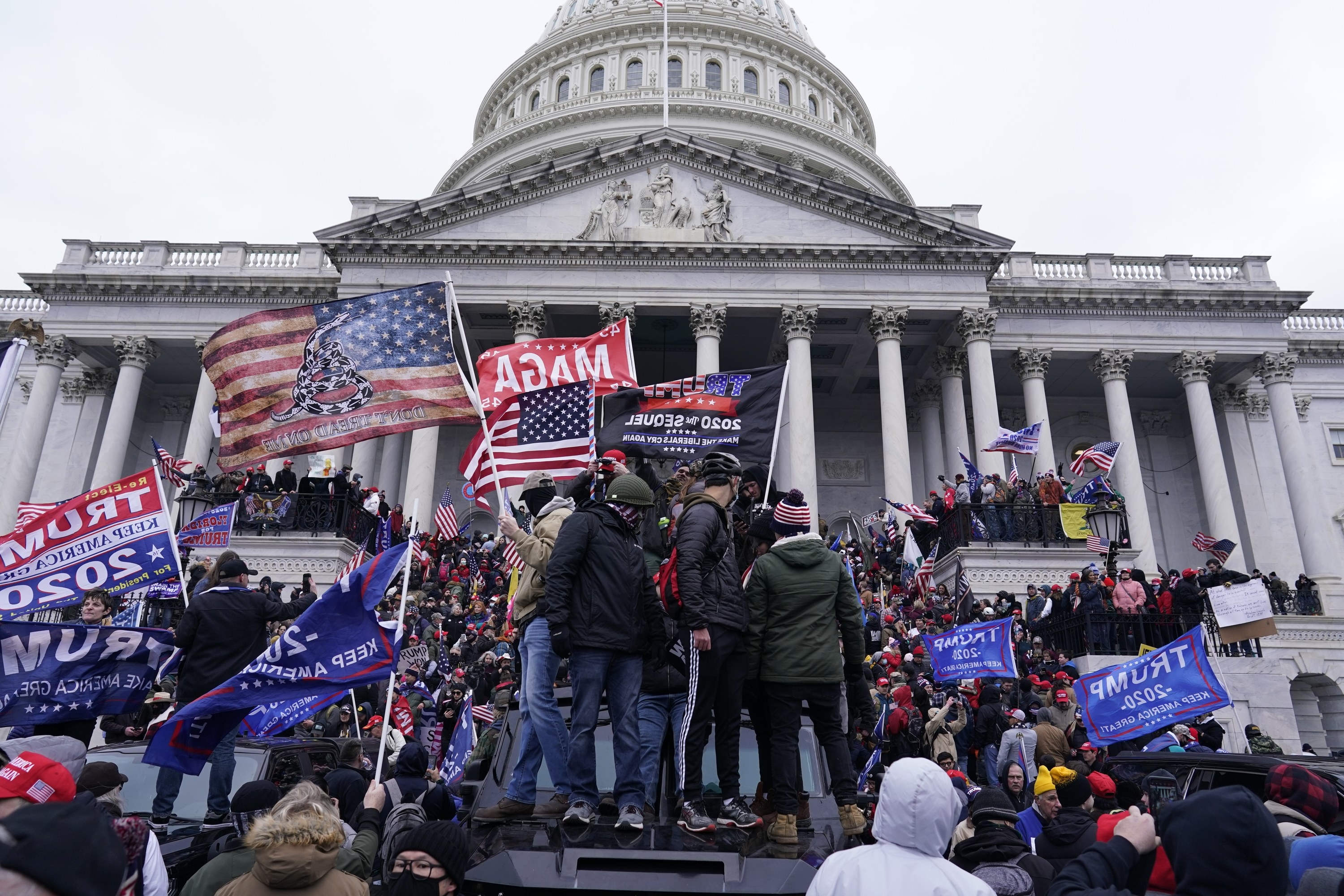 "A mob of Trump supporters, waving MAGA and ""Trump 2020"" flags, stand outside the US Capitol building, some standing on top of an armored car"
