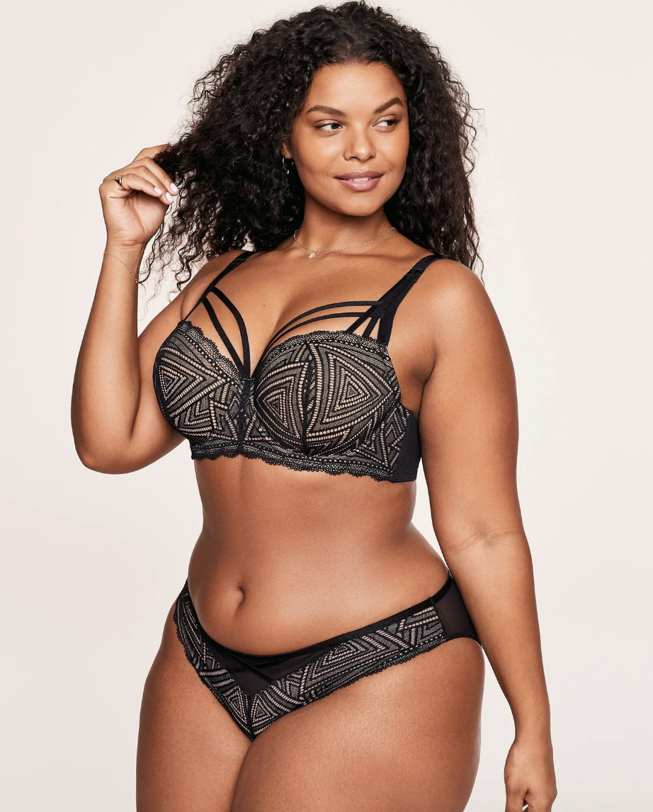 Model in a black patterned bra with straps on top of the cups and matching underwear