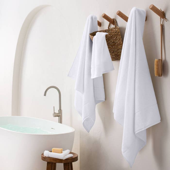 Four sizes of the towel hanging in a bathroom, shown in white.