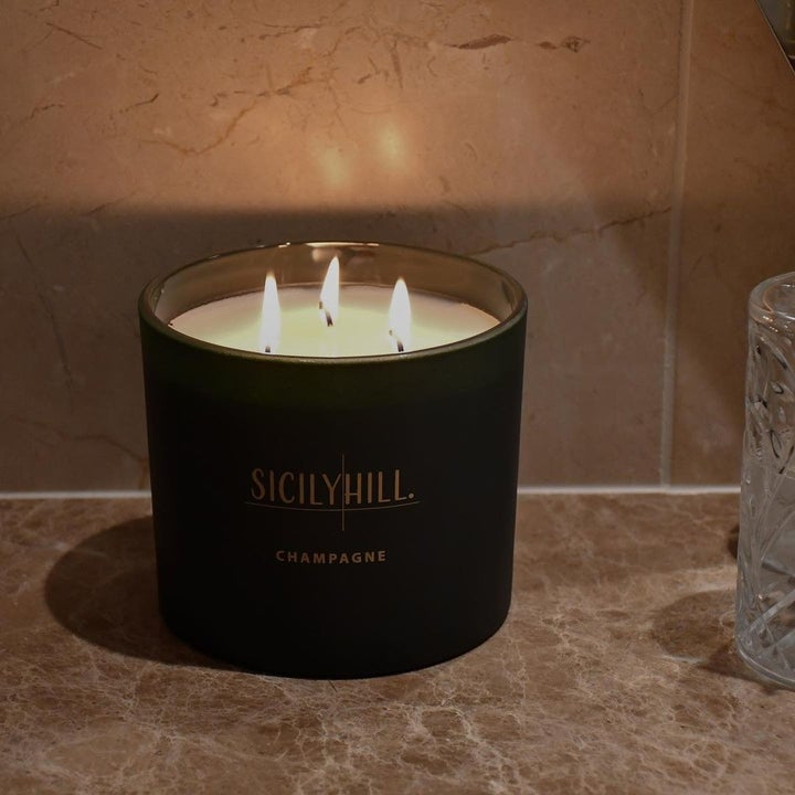 a black candle with sicilyhill champagne written on it in gold and three wicks