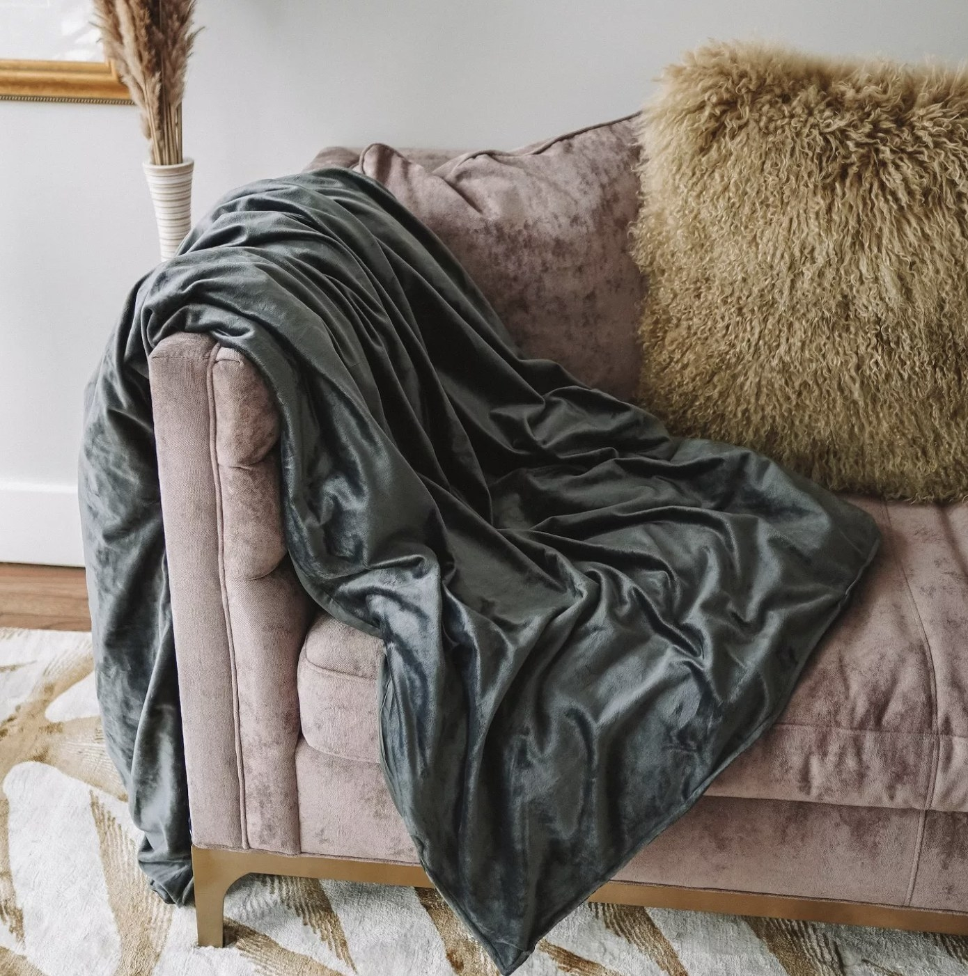 The dark grey blanket draped on a couch