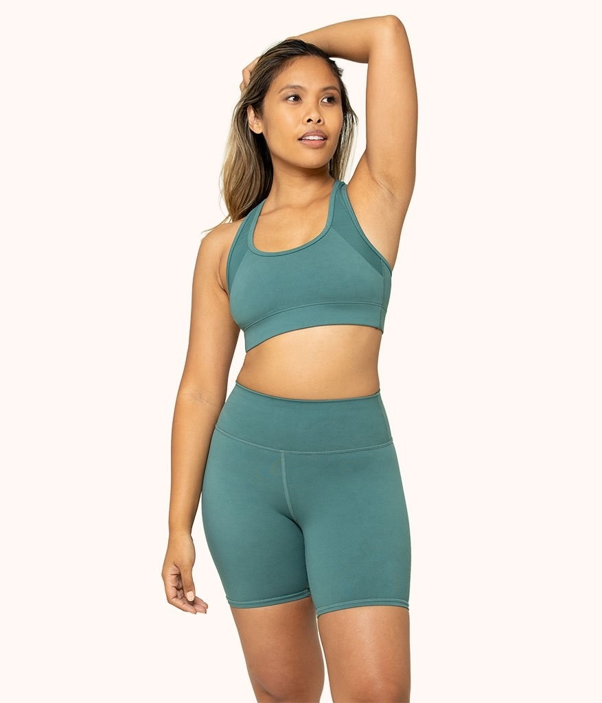 model wearing the mid-thigh length shorts in green