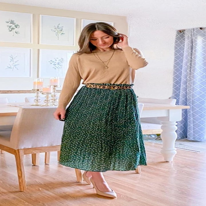 A reviewer wearing the skirt in green