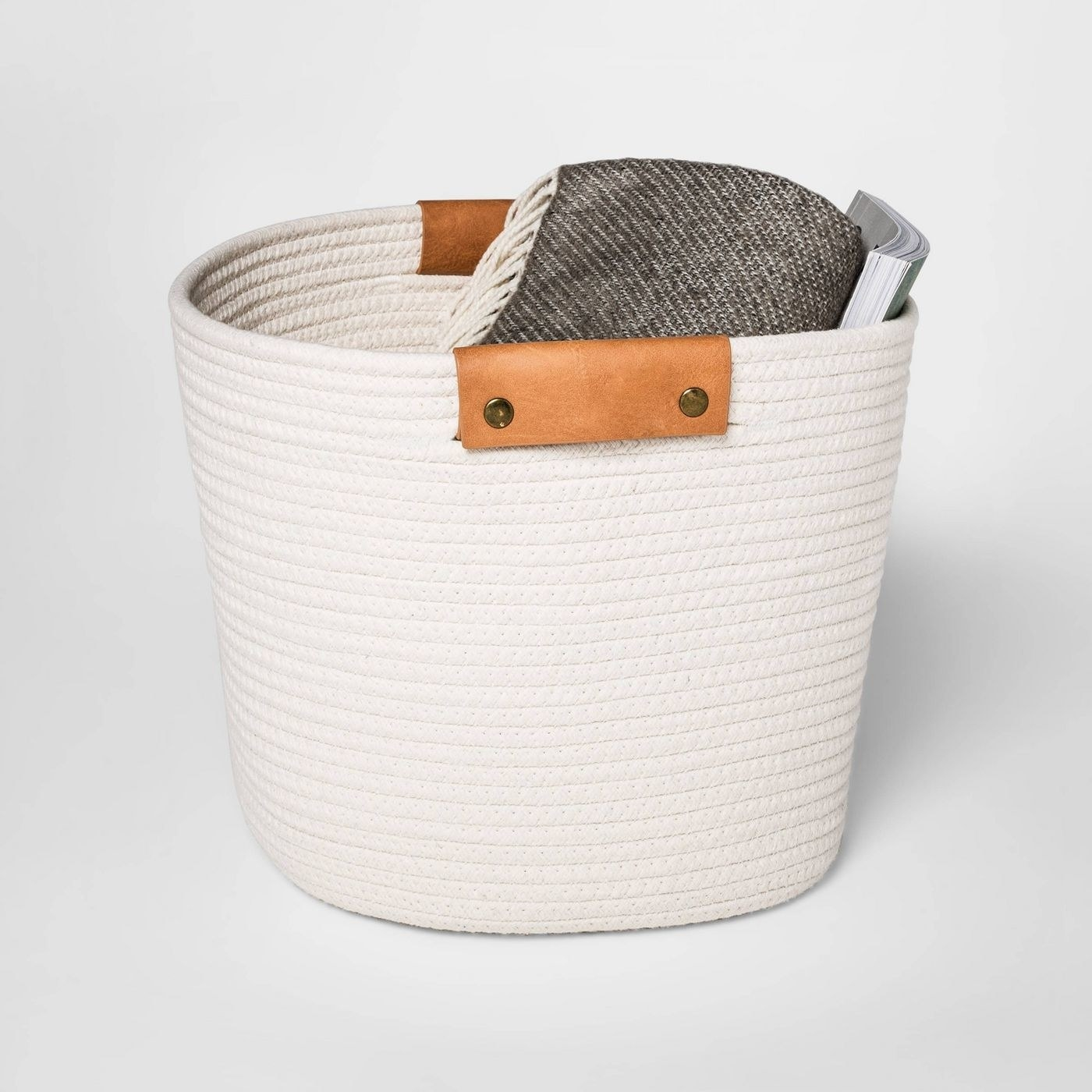 The basket with a blanket and a magazine in it.