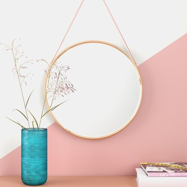 The mirror, which is round with rose gold frame, and has a chain extending from the top of the frame to be visible when it is hung