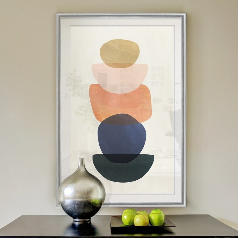 The print, which is rectangular, and has circle, half circle, and rectangular shapes, stacked on top of each other, in blue, black, peach, and gold tones