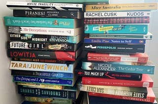 Two tall stacks of books showing a variety of colourful titles