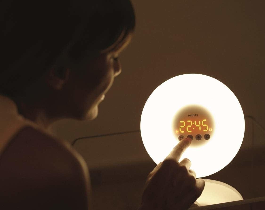 A woman setting an alarm on the wakeup light.