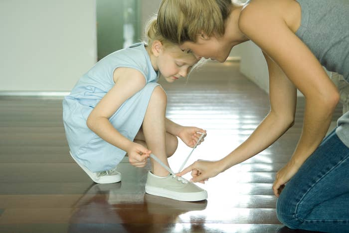 A woman helping a child tie her shoe