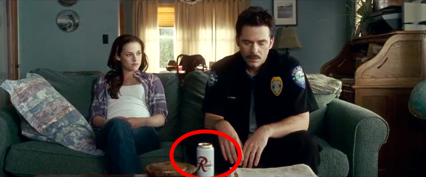 Bella and Charlie Swan sitting on a couch with a can of Rainier beer sitting on a table in front of them