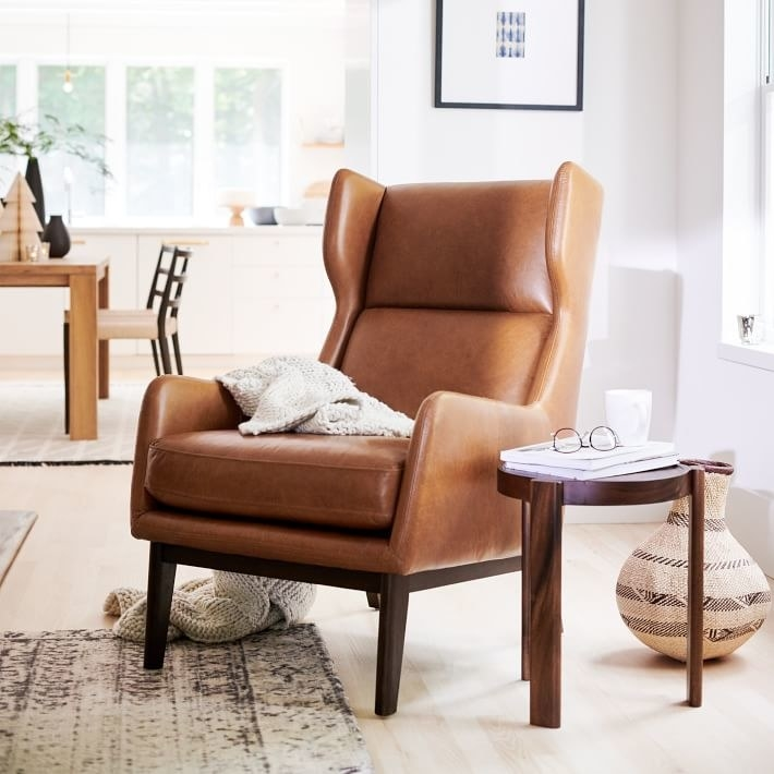 a brown leather chair with dark brown wooden legs