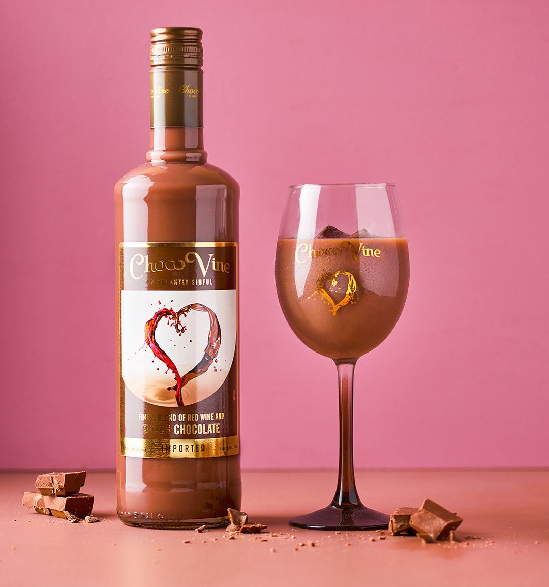 Bottle of ChocoVine next to a wine glass filled with the chocolate wine drink