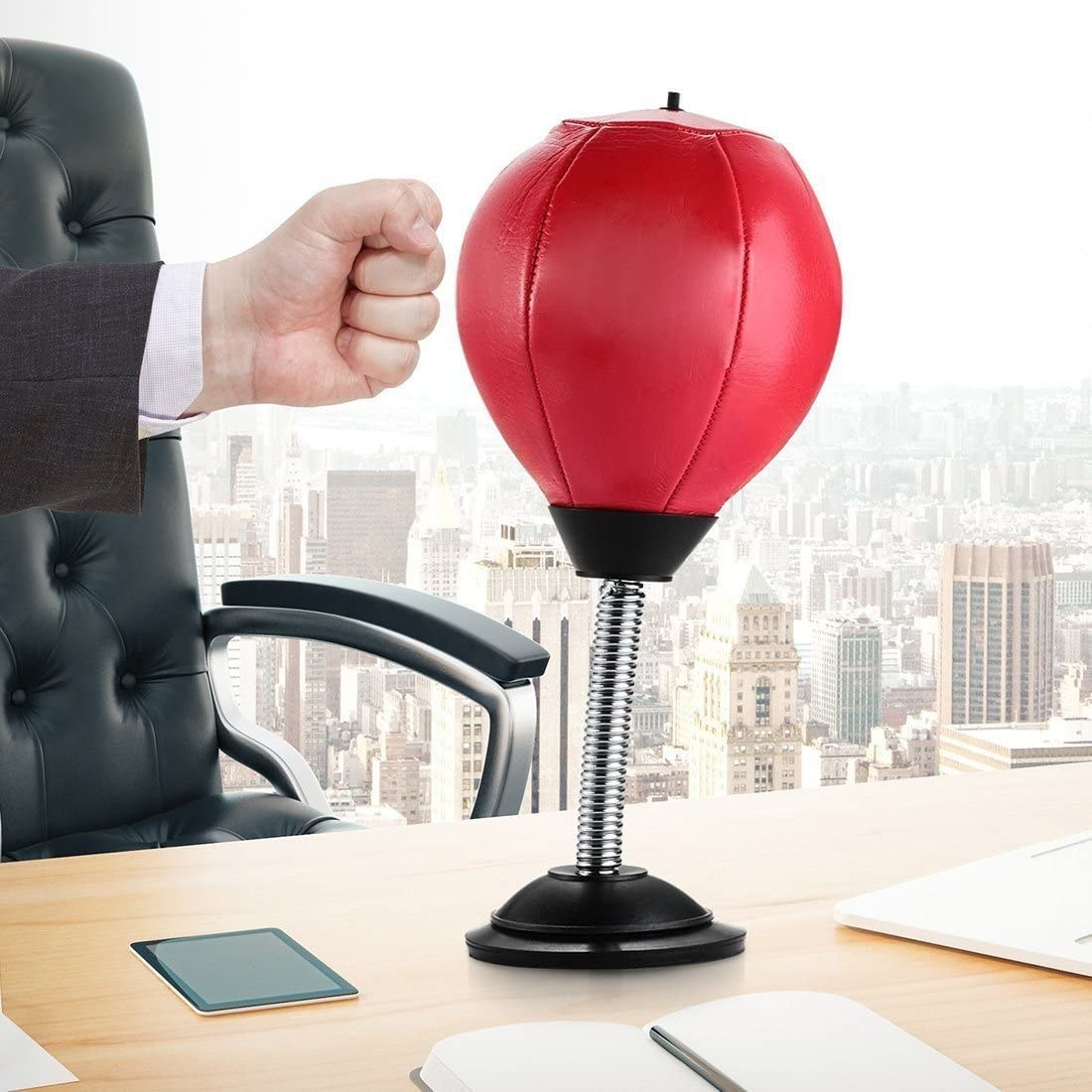 A hand punching the bag, which is attached to the top of a desk