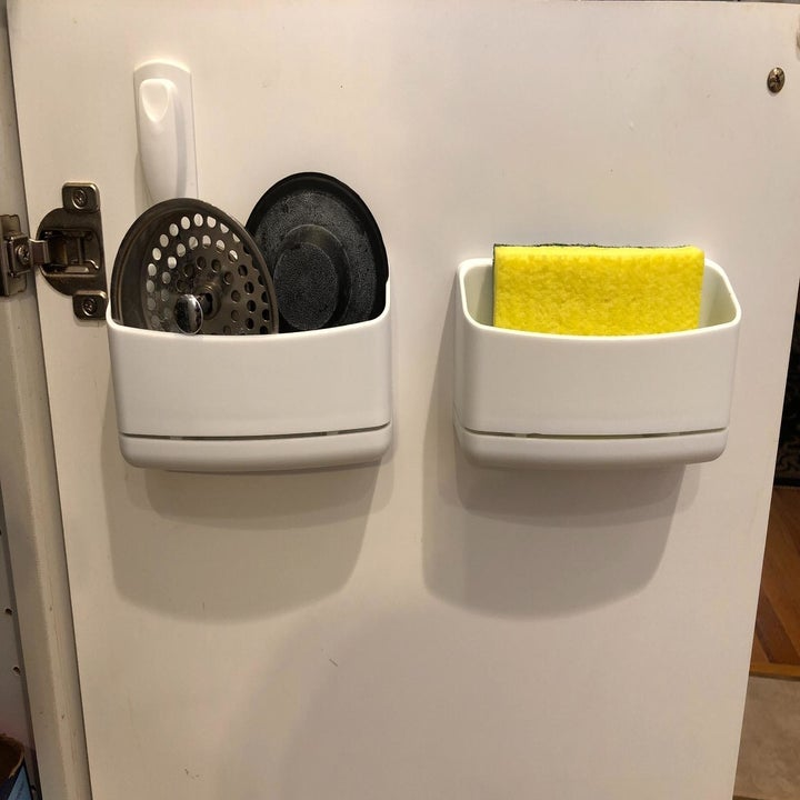 Two of the caddy's on the inside of a reviewer's cabinet door, holding drain plugs and a sponge