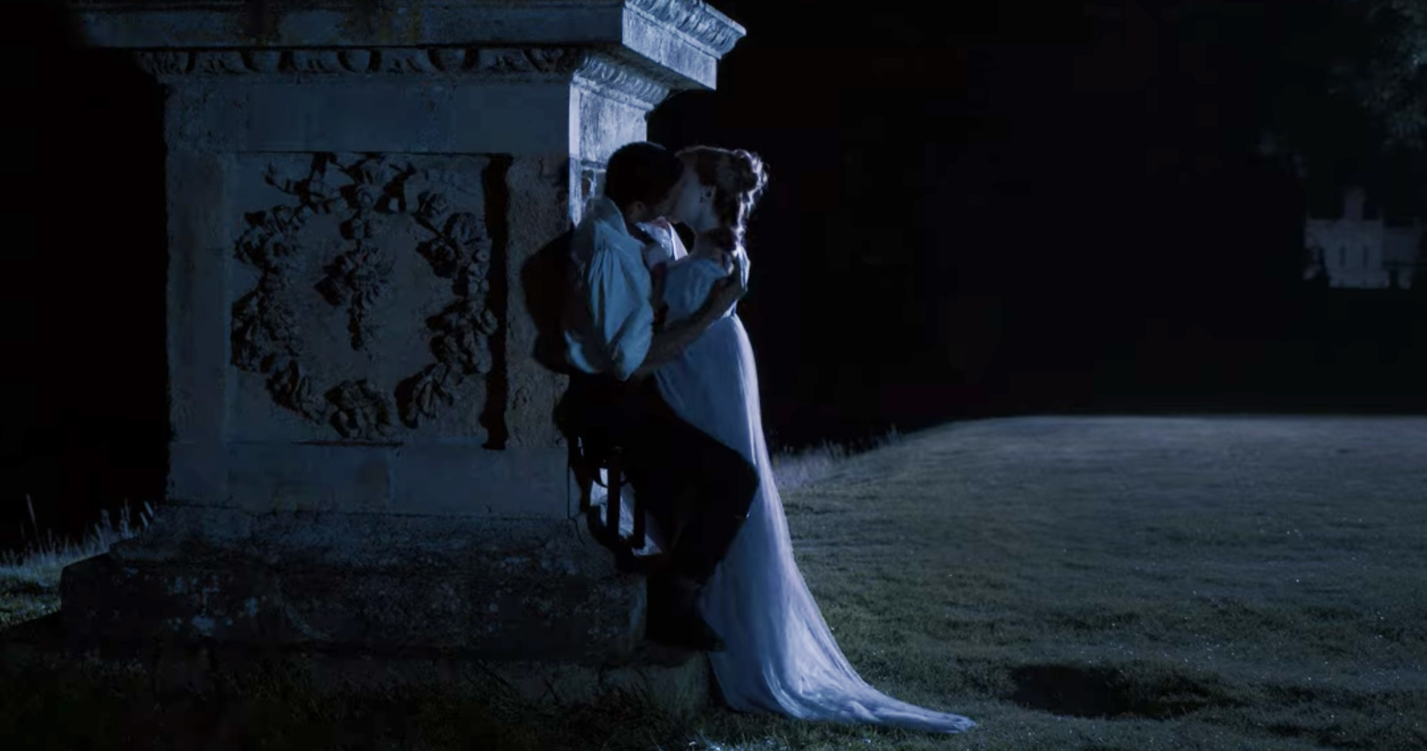 Simon and Daphne passionately kissing against a statue outside