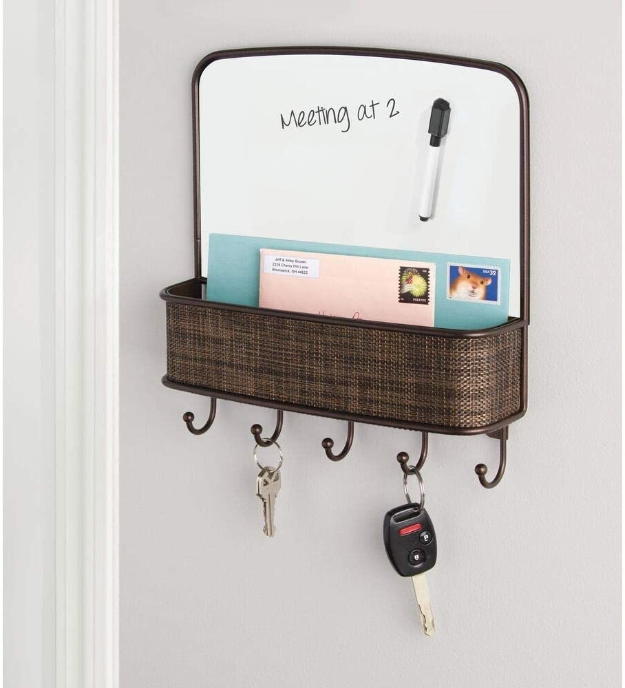 the brown metal and woven organizer with five hooks on the bottom mounted on a wall