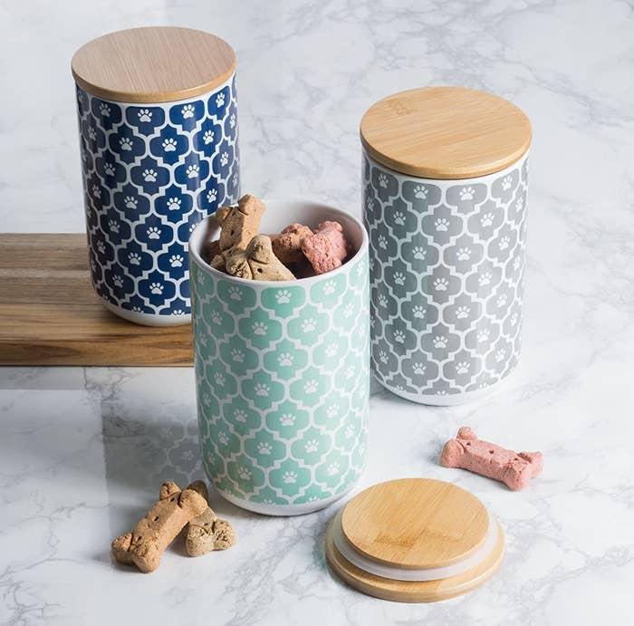 Three ceramic jars with lids and dog treats inside