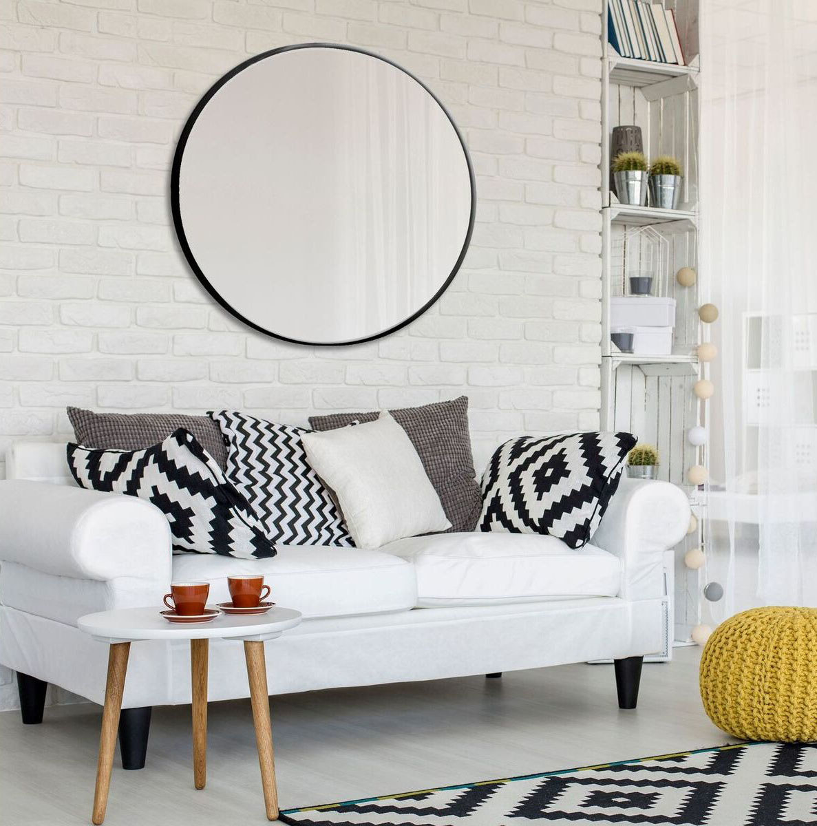 The black-framed mirror on a brick wall in a living room scene