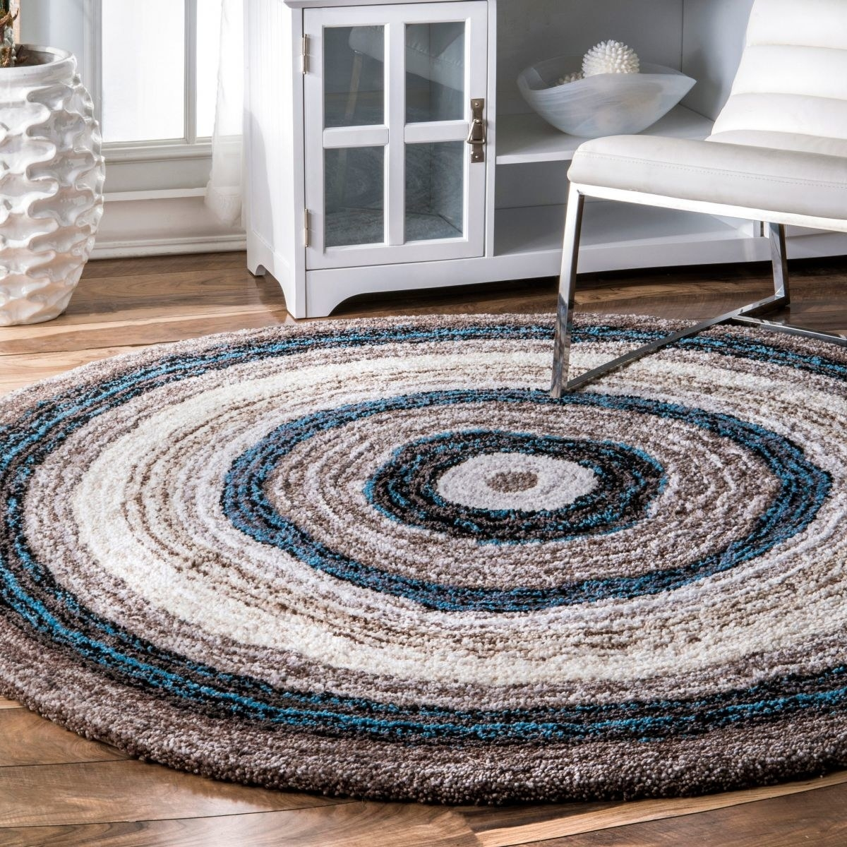a circular shag rug with blue, white, tan, and brown designs in it