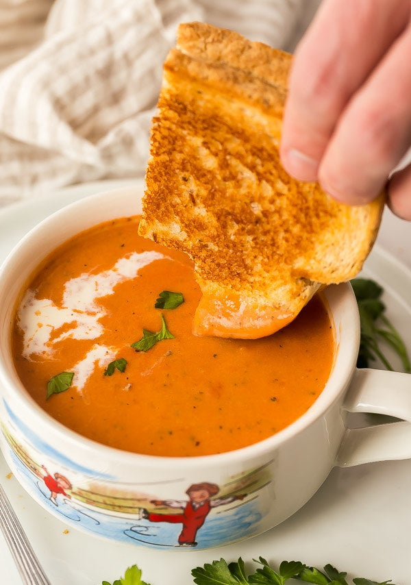 Dunking grilled cheese into a bowl of creamy tomato soup.