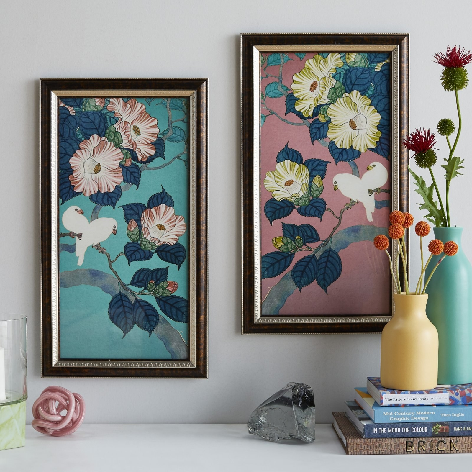 The two paintings of birds and flowers, one with blue backdrop and one with pink