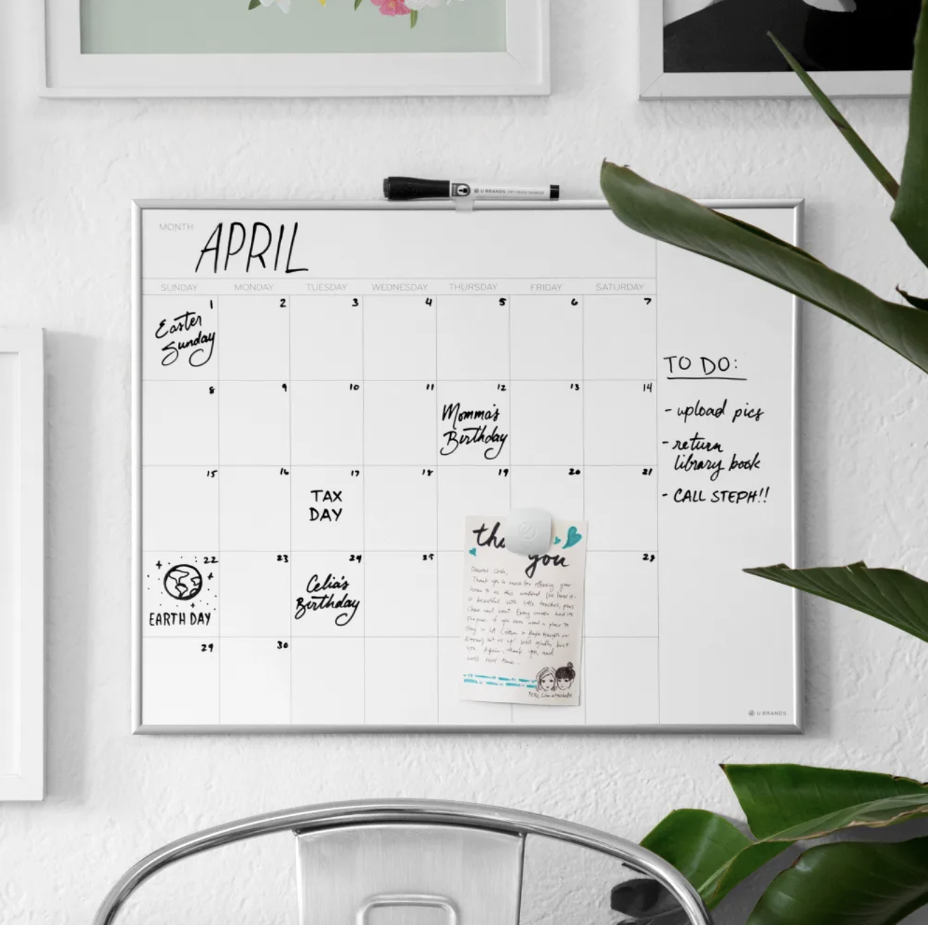 the U Brands Magnetic Dry-Erase White Calendar Whiteboard mounted on a wall with written notes on it