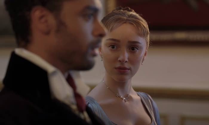 Phoebe Dynevor as Daphne Bridgerton staring at Regé-Jean Page as the Duke of Hastings