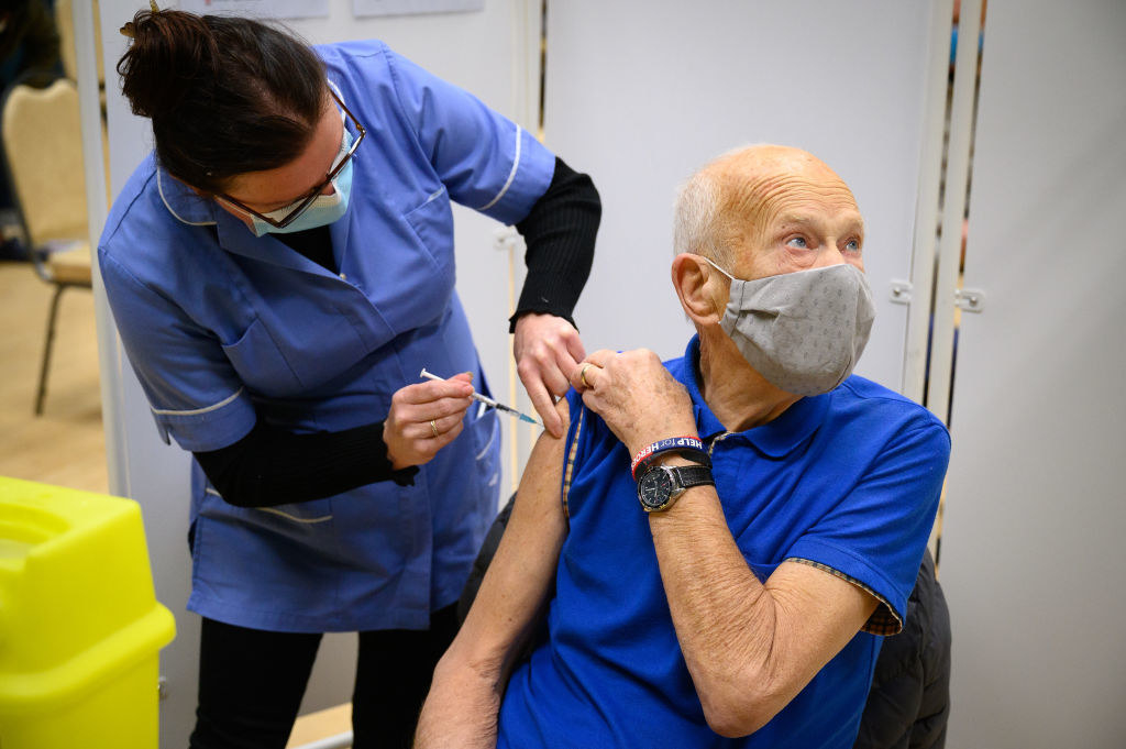 An older man looking away as he receives the vaccine