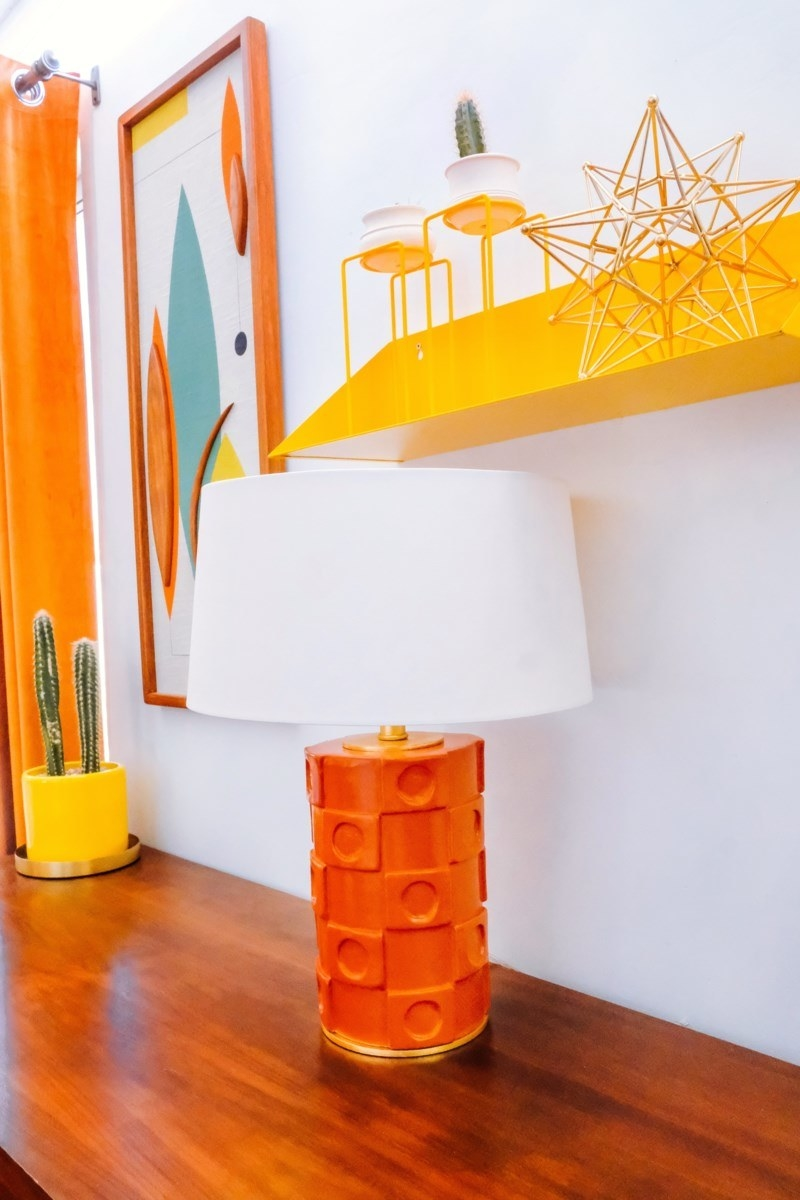 a lamp with an orange base and squared designs around it with a white shade