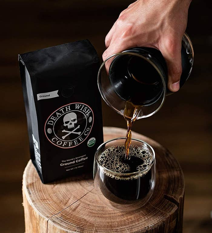 bag of coffee with a skull and crossbones on it next to someone pouring coffee into a mug