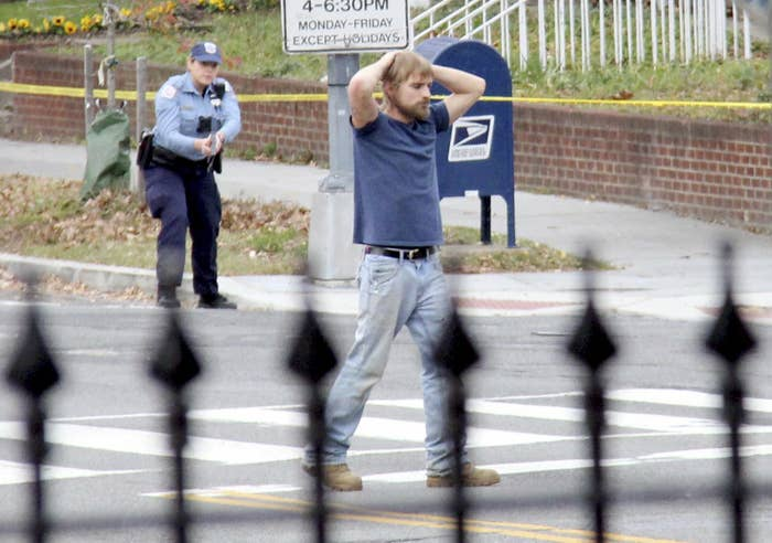 A white man stands at a crosswalk with his hands on his head while a police officer with her gun drawn stands several yards behind him
