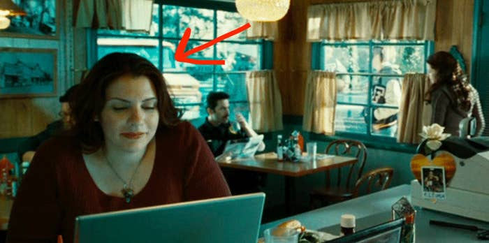 Stephenie Meyer at a laptop in a diner with Charlie and Bella Swan behind her