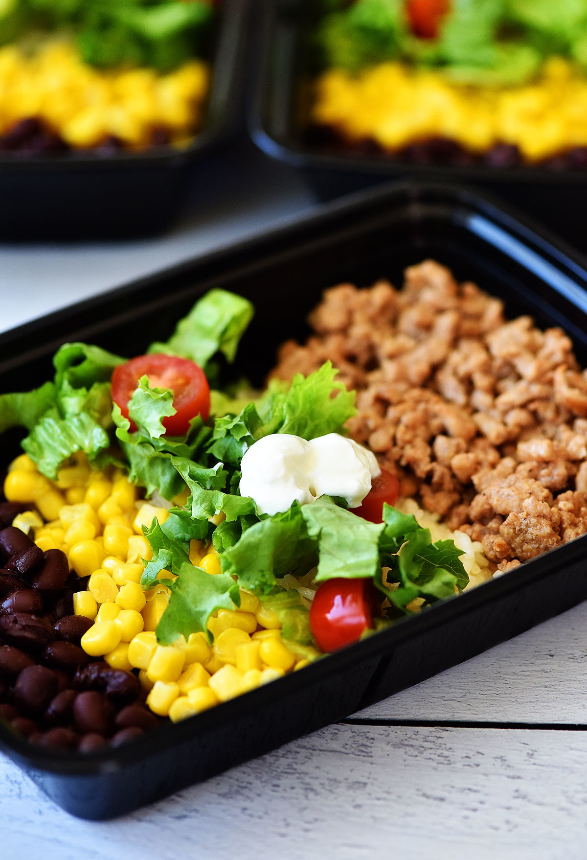 Meal prep bowls with ground turkey meat, lettuce, corn, black beans, and tomato.