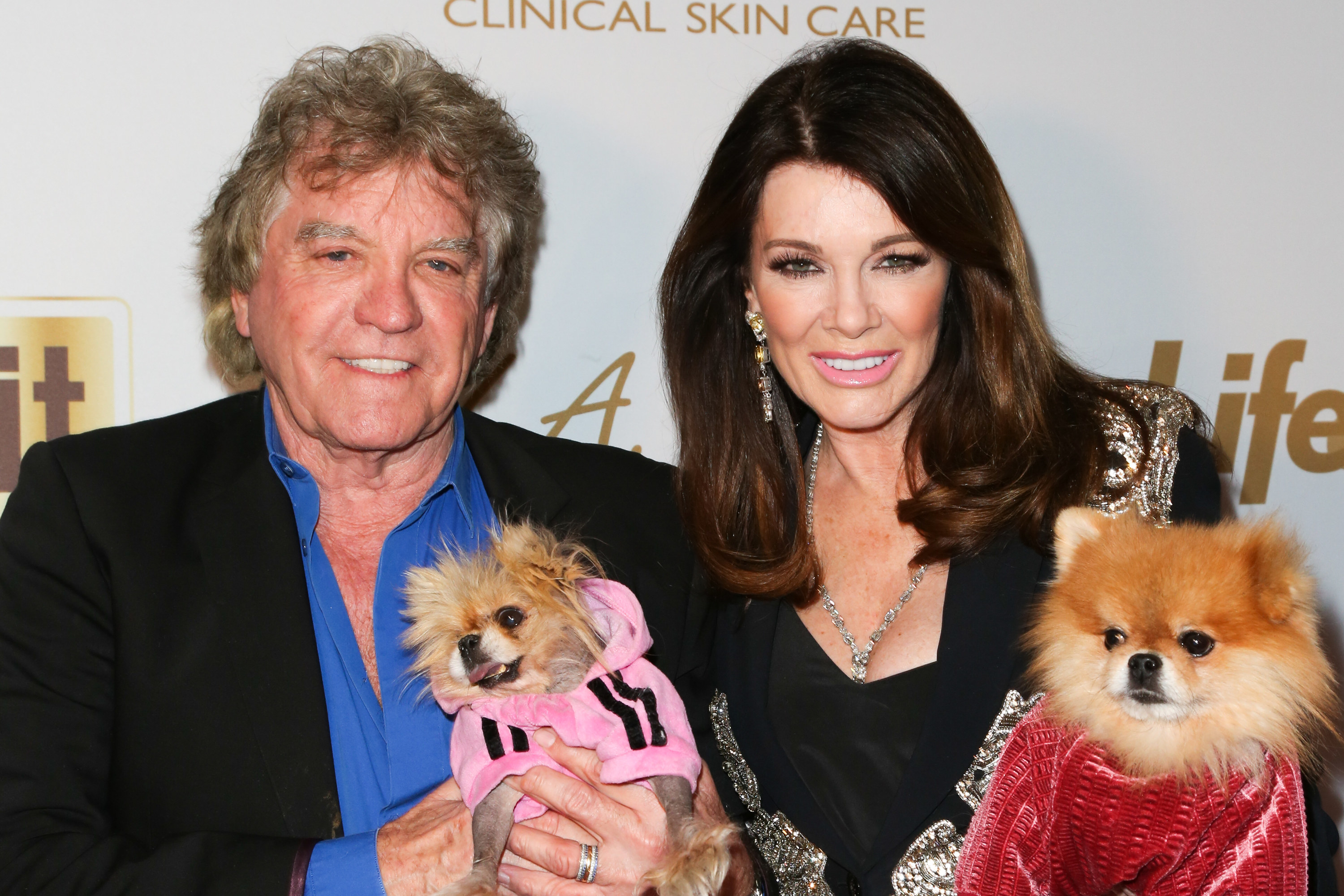 Ken and Lisa posing on a red carpet with two of their dogs