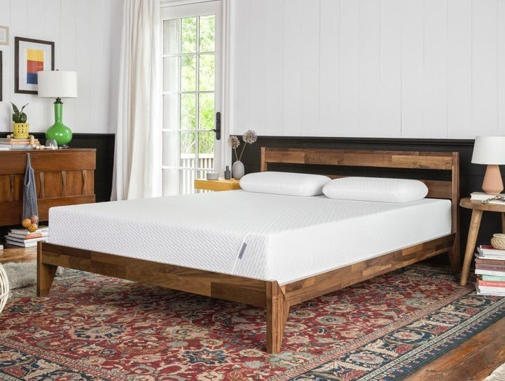 white mattress in a wood bed frame