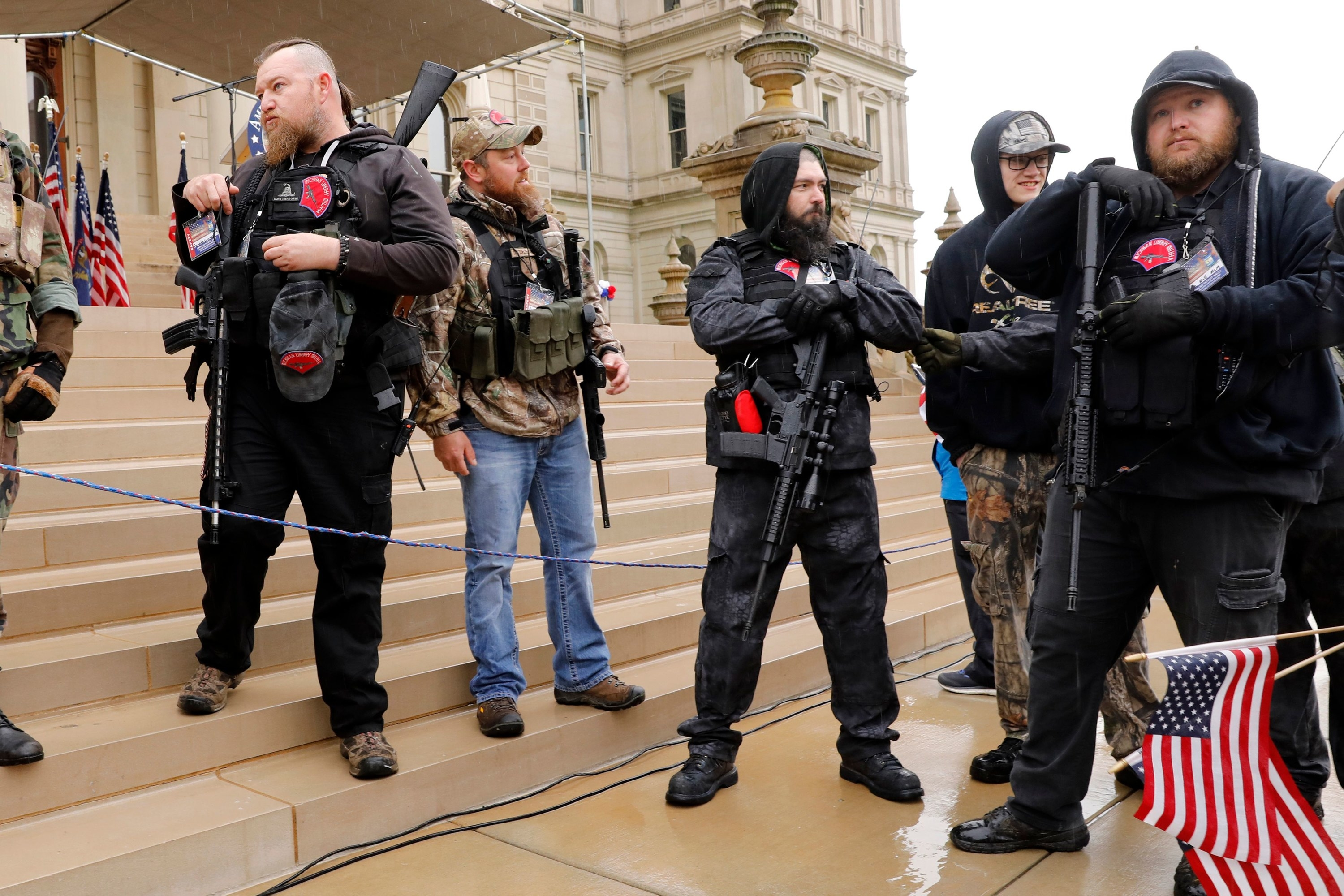 White men armed with large guns stand on the steps outside the state capitol building