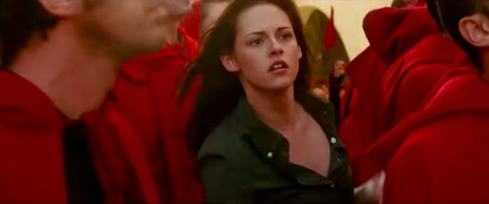 Bella searching a crowd of people in robes
