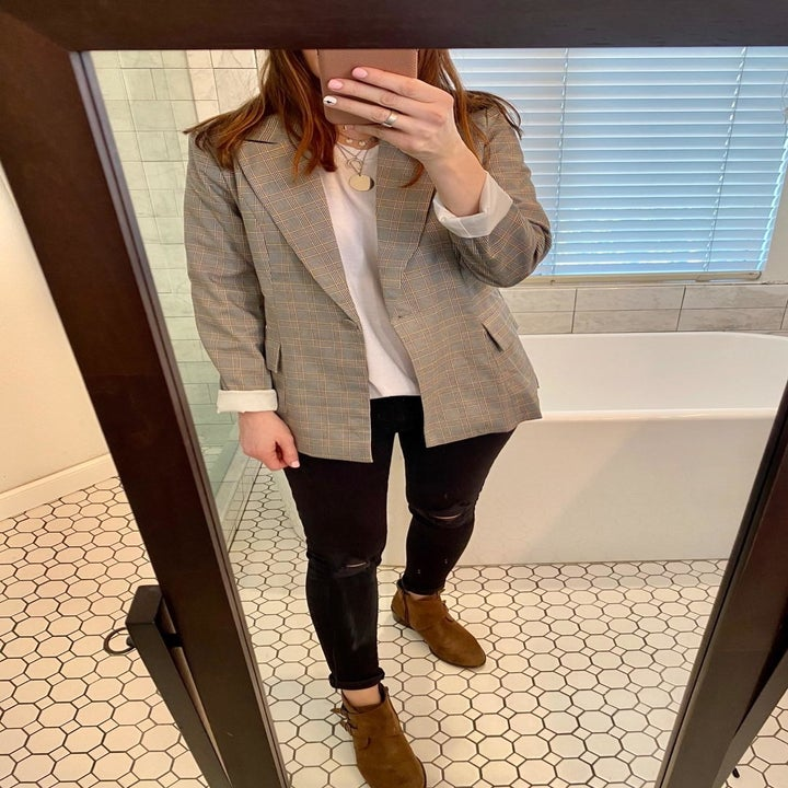 The same reviewer styling the plaid blazer with a white t-shirt, black jeans, and brown booties