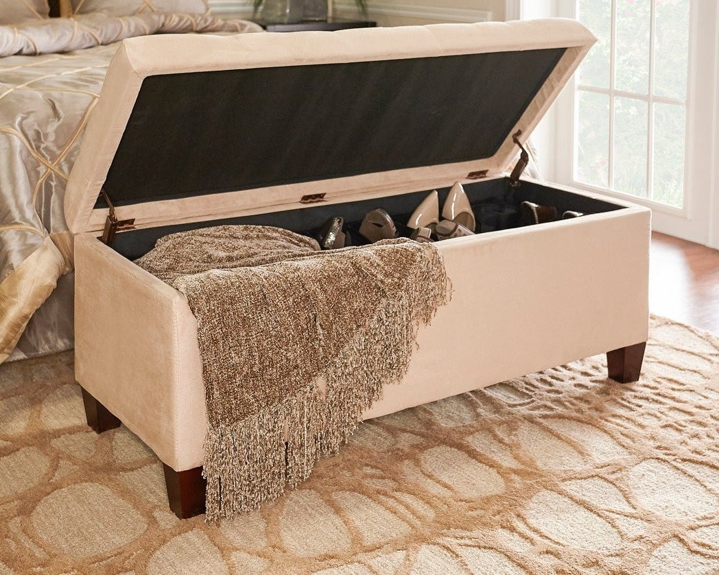 beige ottoman with square wood legs, lid open revealing the shoe collection