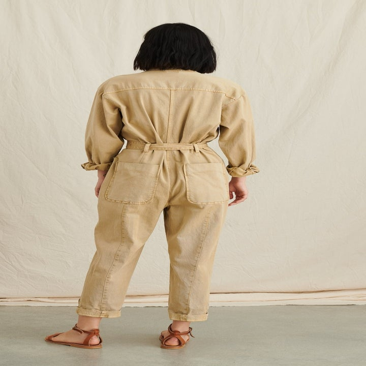 Back view of a model wearing the jumpsuit in vintage khaki