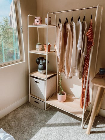 Reviewer's light wood garment rack with pink blouses, a red dress, and storage shelves displaying a camera, sculptures, and succulents