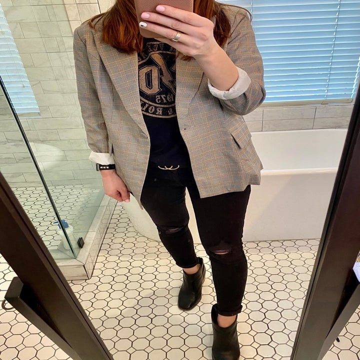 A reviewer's photo of the plaid blazer styled with a graphic tee, ripped black jeans, and black booties